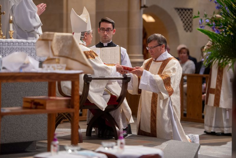 Deacon Brian Mizzoni is presented with the Book of the Gospels.