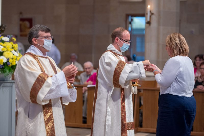 Deacons Brian Mizzoni and Aaron Kelly distribute Communion.