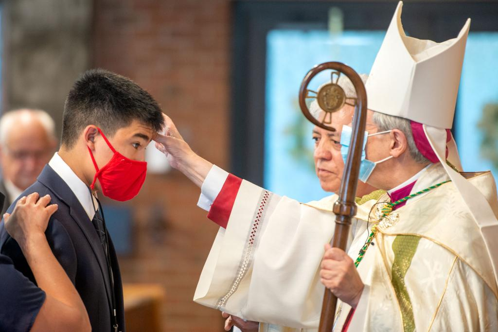 Bishop Salvatore R. Matano anoints Derrick Morales during the confirmation.
