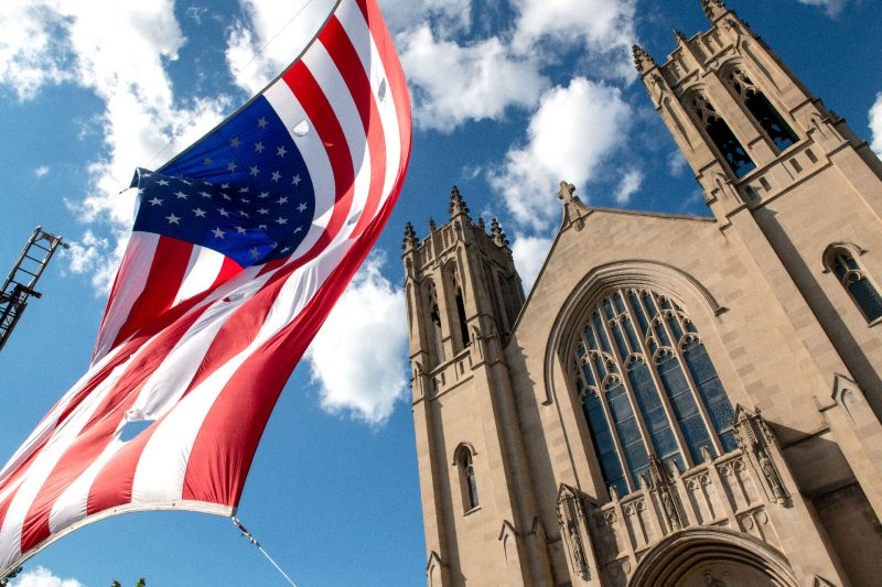 An American flag flies between two fire trucks in front of Rochester's Sacred Heart Cathedral Sept. 11 during a Mass recognizing first responders on the 20th anniversary of the Sept. 11, 2001, terrorist attacks on the U.S.