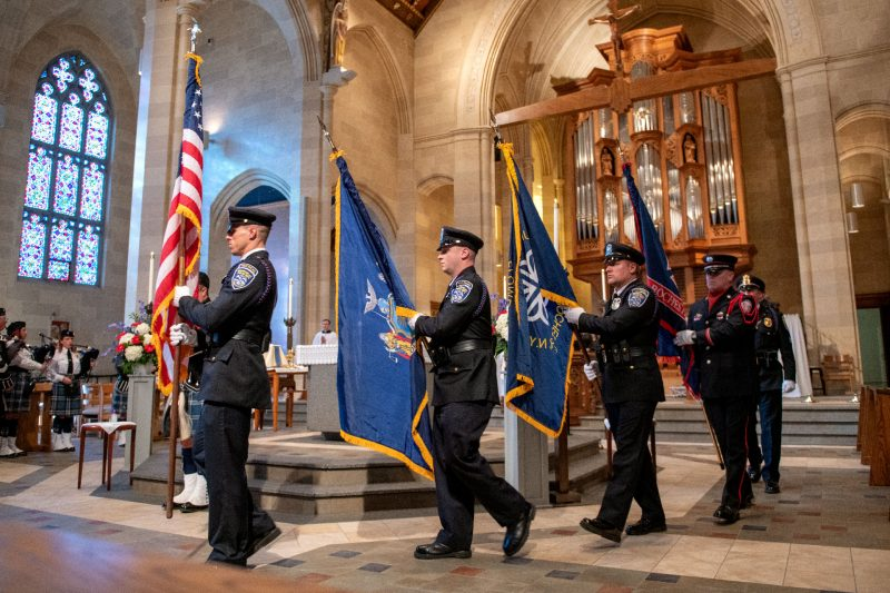 Uniformed flag bearers recess from the cathedral.