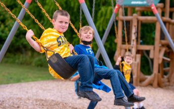 Caleb Brooks (left) and Weston Arseneau (right) swing on the playground at St. Rita School in Webster June 22.