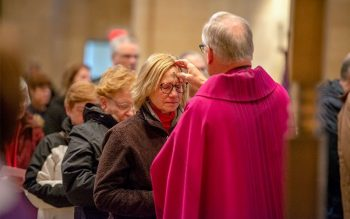Carol Cuomo receives ash from Father Robert Kennedy at Rochester's Sacred Heart Cathedral.