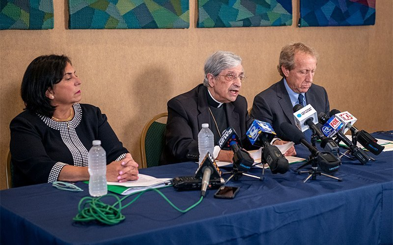 Bishop Salvatore R. Matano (center) speaks to the media at the diocesan Pastoral Center in Gates during a Sept. 12 press conference regarding the diocese's Chapter 11 bankruptcy filing earlier that day. He is flanked by Lisa Passero, diocesan chief financial officer, and diocesan attorney Stephen Donato. (Courier photo by Jeff Witherow)