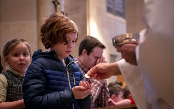 Canandaigua's St. Mary School student Charlie Robak receives Communion during the Feb. 27 Catholic School's Week Mass, celebrated by Bishop Salvatore R. Matano at Rochester's Sacred Heart Cathedral.