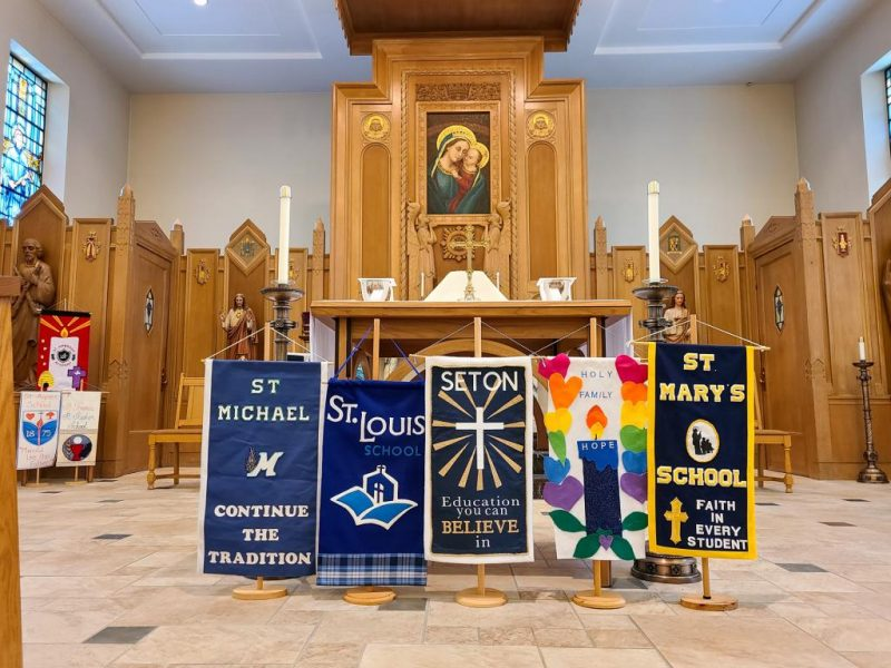 Banners recognizing diocesan Catholic schools are seen in the chapel before Mass.