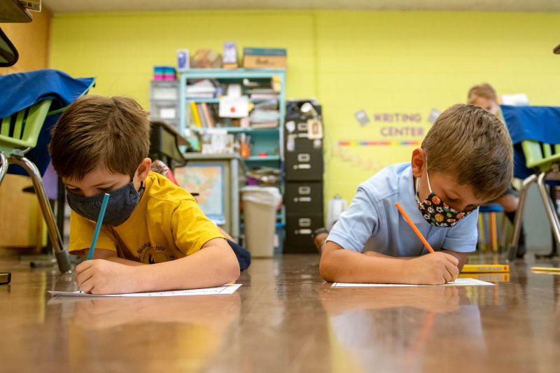 St. Mary School second-graders Sebastian Lefebvre (left) and Ethan West color pictures on their classroom floor Sept. 9.
