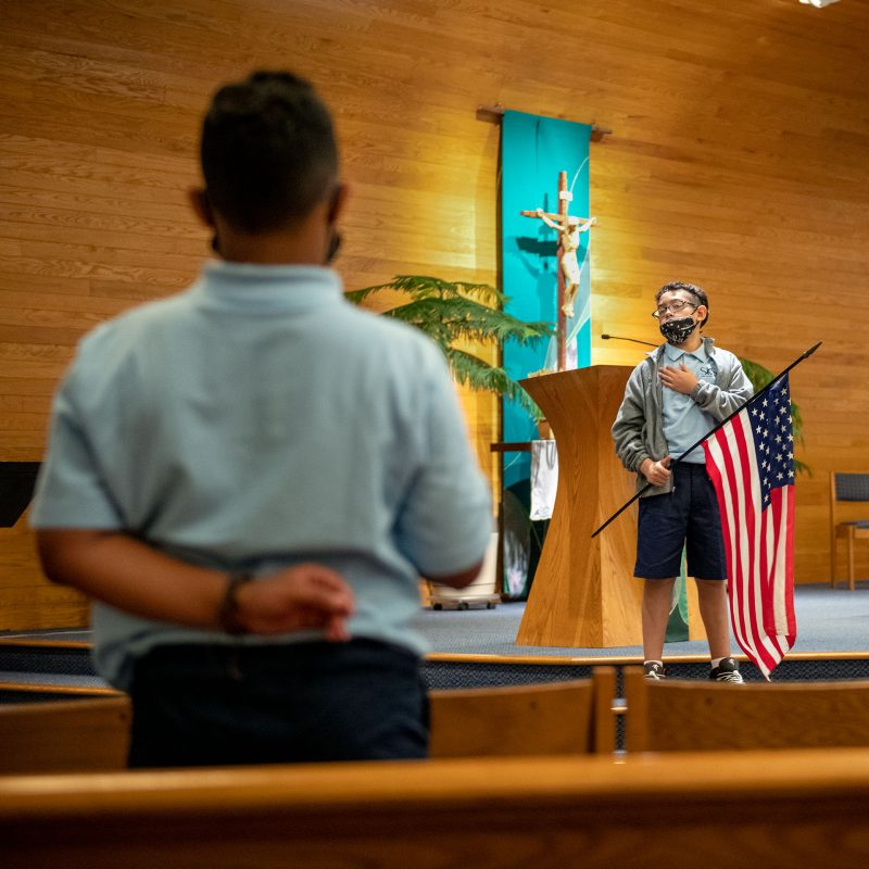 Marlon Rivas holds the American flag for the national anthem during a prayer service on the first day of the 2021-22 school year at St. Kateri School Sept. 8.
