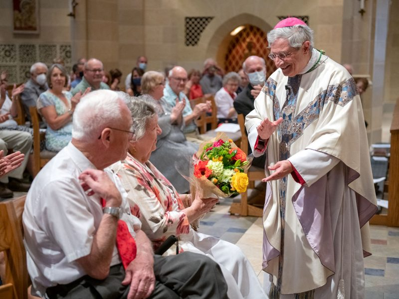 Bishop gives flowers to elderly couple