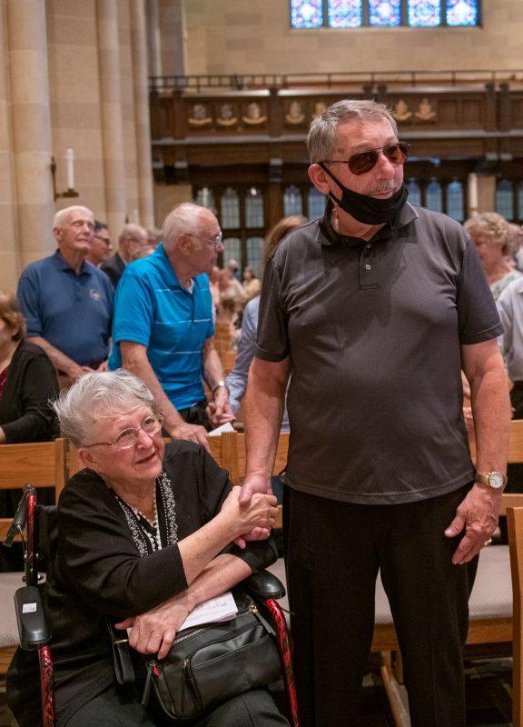 An elderly couple holds hands.