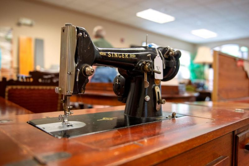 An antique Singer sewing machine and table is displayed in the sale's furniture room.