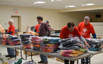 People sort though donated clothing.