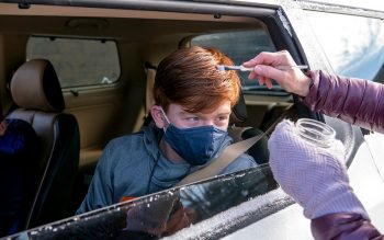 Tyler Hancock receives ashes at St. John of Rochester Church in Fairport while sitting in the back seat of his family's car.