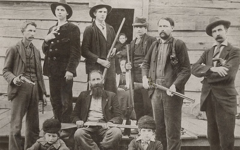 William Anderson Hatfield, known as Devil Anse, sits cross-legged with his rifle across his lap.