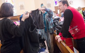 Gina Crawford ,left and Greg Fassler help Linda Malowsky pick out coats during the Christmas giveaway at Holy Apostles Church in Rochester on Dec. 19. More than 100 families were helped by the event which also included a food basket. (Courier photo by John Haeger)