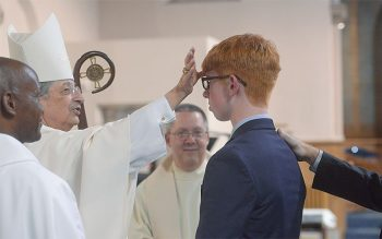 Will Thomas of St. Catherine of Siena in Ithaca is anointed by Bishop Salvatore R Matano during the celebration of the Sacrament of Confirmation May 16. (Courier photo by John Haeger)